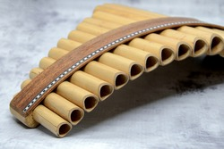 Close-up of woodwind instrument pan flute. Details of musical instruments, music. Selective focus, blurred background.