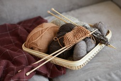Close-up of wool and needles for knitting on the sofa