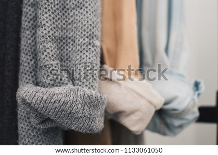 Close up of woolen cardigan, linen and denim jackets rolled up sleeves. Cozy and minimal lifestyle, capsule wardrobe. Selective focus, horizontal