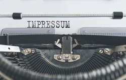 close-up of word IMPRESSUM, German for copyright page or imprint or publishing information, written on old manual typewriter