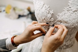 Close-up of work process of a fashion designer at her studio. Hand sewing bridal gown / dress process. Pin lace to dress on a mannequin.
