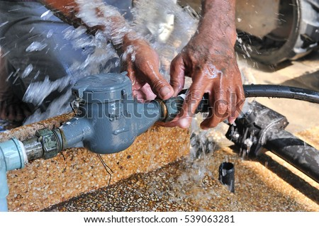Close-up of worker hands plumbing unscrew connecting pipe while water leak, selective focus