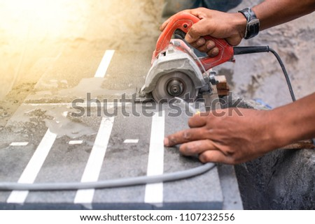 Close up of worker making cut sandstone by electric hand stone saws, working with power tools