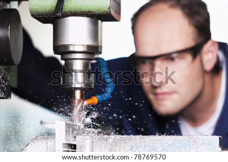 Close up of worker with safety glasses at milling machine in workshop.