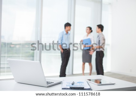 Close-up of workplace in modern office with business people behind