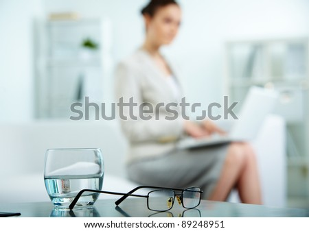 Close-up of workplace with glass of water and eyeglasses on it and businesswoman typing on background