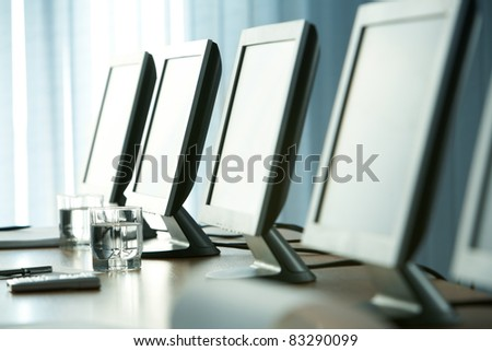 Close-up of workplace with glass of water, some objects and monitors on it - stock photo