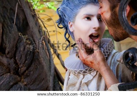 Close-up of wounded male vampire touching young medieval woman's bleeding lips