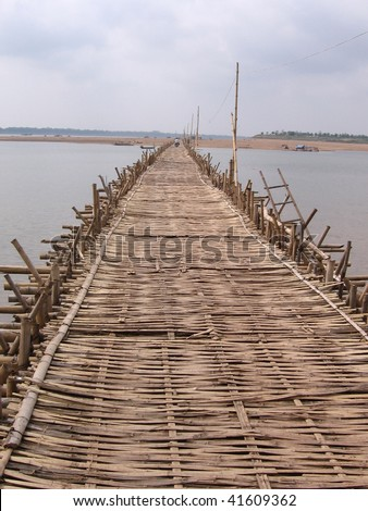close-up of woven bamboo bridge leading to an island on the horizon