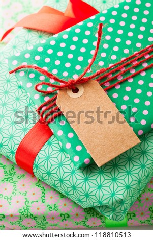 Close up of wrapped gifts with red ribbon and plain cardboard tag