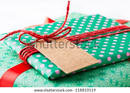 Close up of wrapped gifts with red ribbon and plain cardboard tag on white background