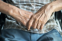 Close up of wrinkled hands of disabled old man in wheelchair
