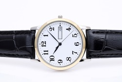 close up of wristwatch with leather strap on white background