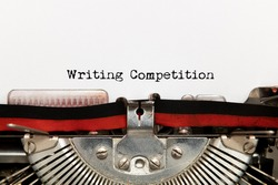 Close up of writing competiotion title text printed on white paper with vintage typewriter contest concept