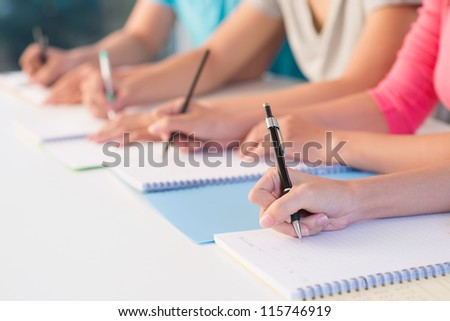 Close-up of writing hands of students at school