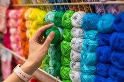 Close Up of yarn balls. Girl hand choosing Yarn in Knitting Shop. knitting shop center. A lot of color yarn for knitting. Selection of colorful yarn wool on shopfront