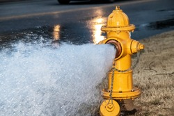 Close-up of yellow fire hydrant gushing water across a street with wet highway and tire from passing car behind