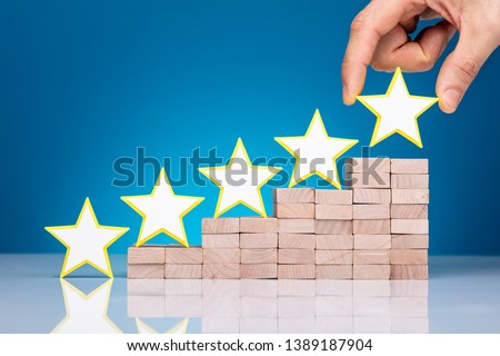 Close-up Of Yellow Star Shape Leading On Top Of Wooden Blocks Over Desk #1389187904