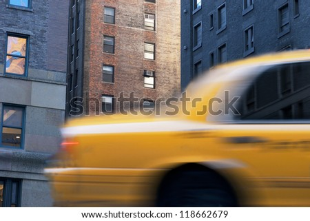 Close up of yellow taxi cab in blurred motion on Street in New York city - stock photo