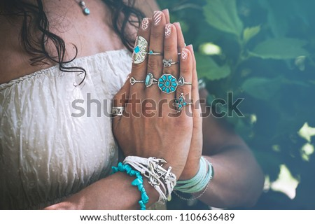 close up of yoga woman hands in namaste gesture with lot of boho style jewelry rings and bracelets outdoor summer day  #1106636489