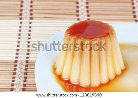 Close-up of yogurt pudding on a plate on decorative wooden napkin.