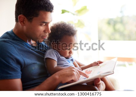 Close up of young adult African American  father reading a book with his two year old son, close up, side view, backlit