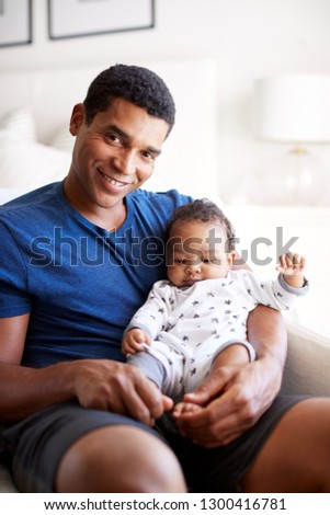 Close up of young adult African American  father sitting in an armchair holding his three month old baby son, smiling to camera, vertical #1300416781