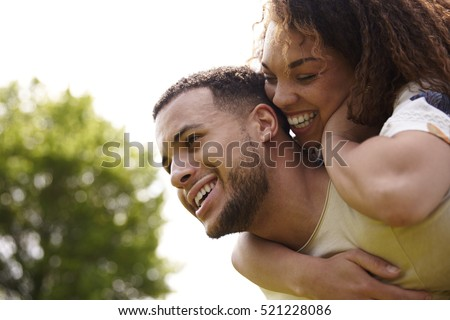 Close up of young adult couple piggybacking outdoors, side view #521228086