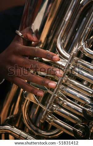 Close-up of young African-American man playing tuba.
