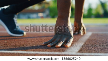 Close up of young african male athlete is launching off the start line in a race in athletics stadium with sunshine.