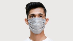 Close up of Young Asian boy wearing mask against the corona virus covid 19 brown man wearing surgical mask to prevent from virus white background face close up young doctor face closeup