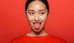 Close up of young asian woman sticking out tongue and looking away. Korean female model making funny face against red background.