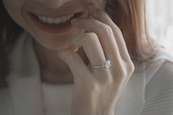 Close up of young Asian woman with natural smile and beautiful diamond ring on her finger.Love and wedding concept.