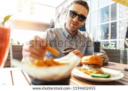 Close up of young attractive man eating french fries and burger at street cafe.