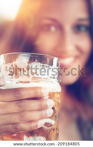 Close-up of young beautiful woman with a glass of beer