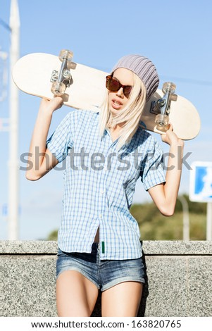 Close-up of young blond girl in beanie hat and leopard sunglasses who stands near granite fence on sunny day holding skateboard on her shoulders
