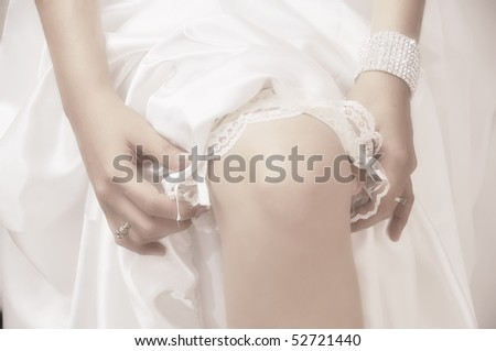 Close-up of young bride putting on white grater
