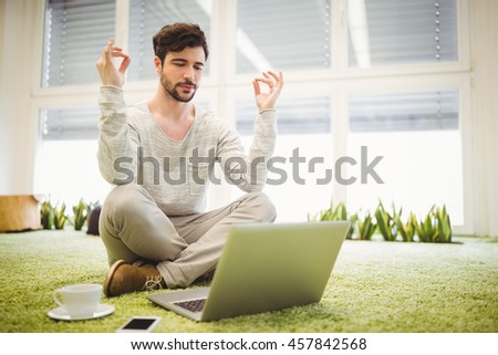 Close up of young businessman doing yoga in front of laptop in creative office