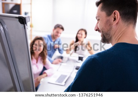 Close-up Of Young Businessman Giving Presentation To His Coworker In Office