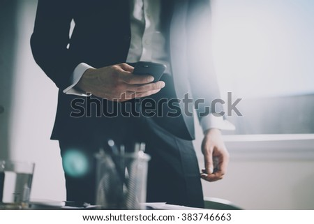 Close up of young businessman in black suit using smart phone while staying at his office, filtered image, male hands with cell phone