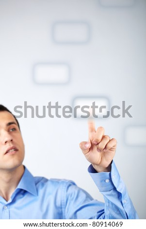 Close-up of young businessman pressing virtual button