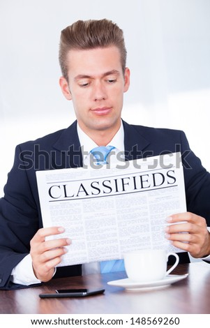 Close-up Of Young Businessman Reading Classifieds On Newspaper