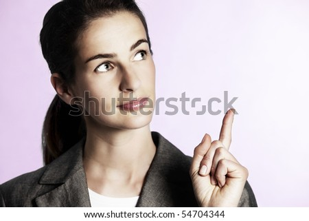 Close-up of young businesswoman pointing upwards.