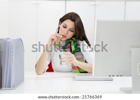 Close-up of young businesswoman putting pill in mouth in office