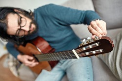 Close up of young caucasian man sitting on sofa at home and adjusting acoustic guitar. Main focus on a guitar. Playing musical instrument. Stay home, self isolation. E-learning. Music education