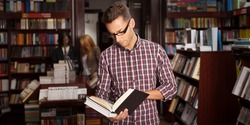 close-up of young caucasian man with eyeglasses in a bookstore with an opened book in his hands reading something with other bookshelves in background