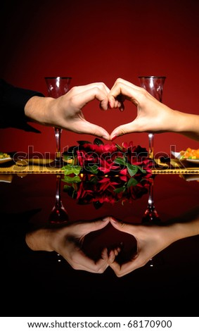 Close up of young couple at restaurant table with hands making a heart shape
