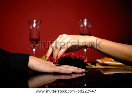 Close up of young couple at restaurant table with woman's hand resting on man's hand.