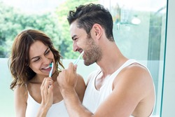 Close-up of young couple brushing teeth in bathroom at home