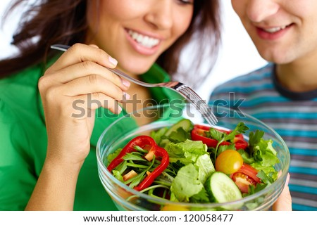 Shutterstock Close-up of young couple eating vegetable salad from glass bowl